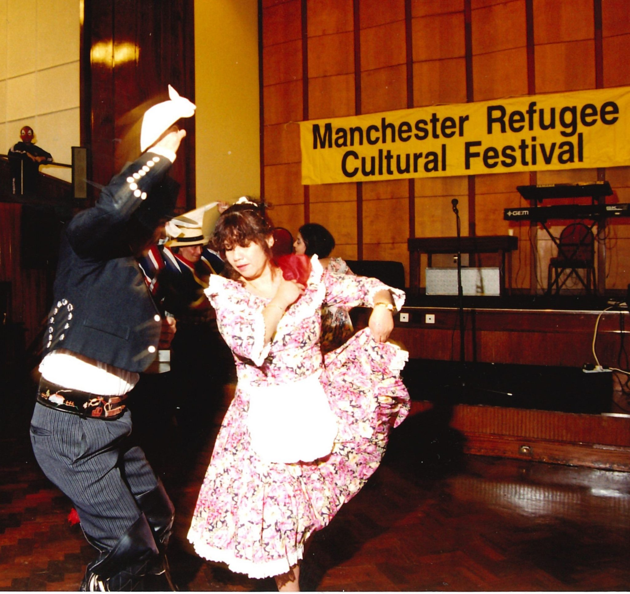 Man and woman dancing in foreground, background sign reading Manchester Refugee Cultural Festival