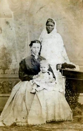 Seated white woman in Victorian clothing with a baby on her lap. Behind her stands an Indian ayah, in traditional Indian clothing.