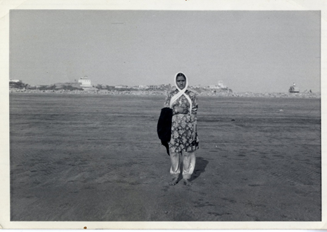 Black and white photo of a young Asian woman wearing traditional Indian clothing. She stands on a wide open area, possibly a beach, with buildings in the distance.
