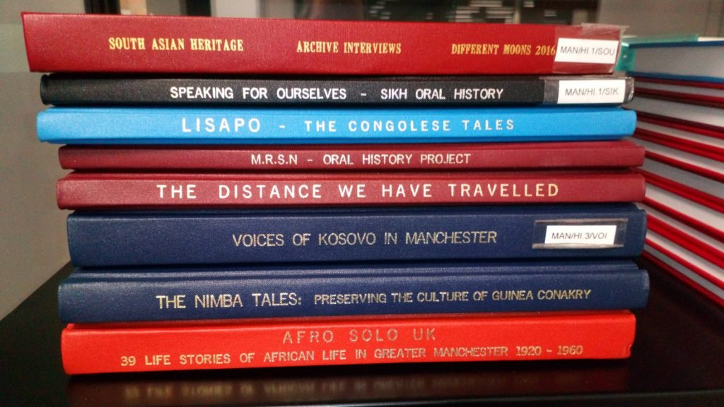 Stack of bound oral histories in various colours