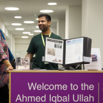 Two people standing at Ahmed Iqbal Ullah RACE Centre desk in Central Library