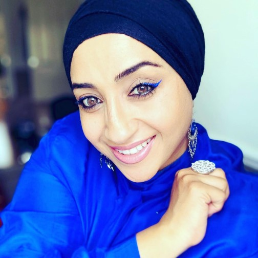 Head and shoulders photograph of Hafsah smiling wearing dark blue headscarf and bright blue top