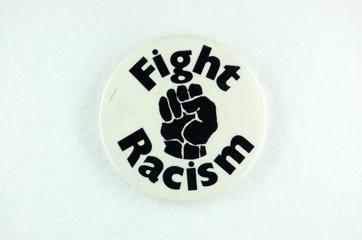 White badge with Fight Racism in black lettering curving around a black raised fist