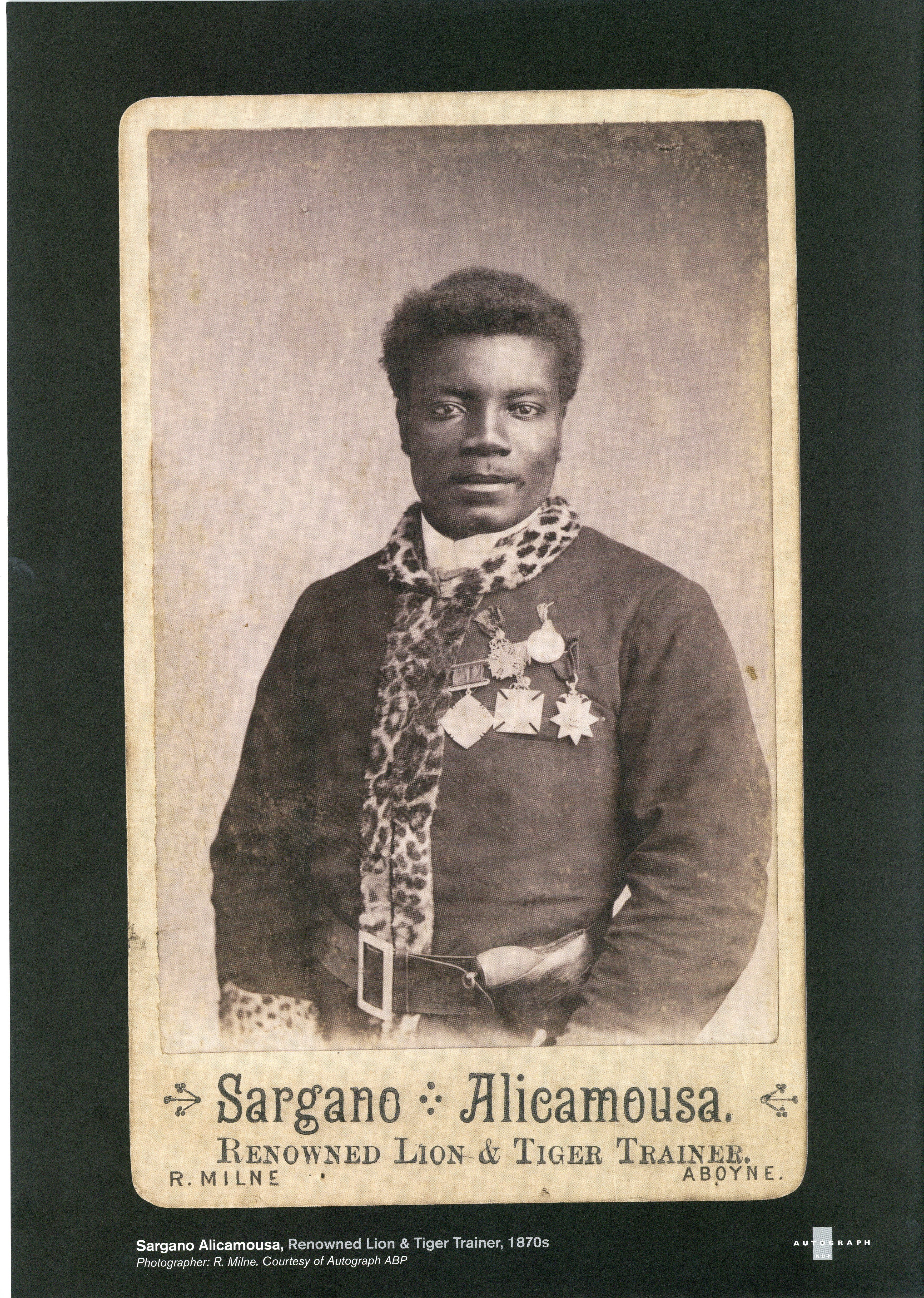 Sepia tinted photograph of a Black man wearing a jacket with medals and a leopard-print scarf. Text below reading Sargano Alicamousa, Renowned Lion and Tiger Trainer 1870s. Photographer R Milne Courtesy of Autograph ABP